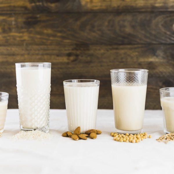 vasos con leche vegetal y puñados de frutos secos delante