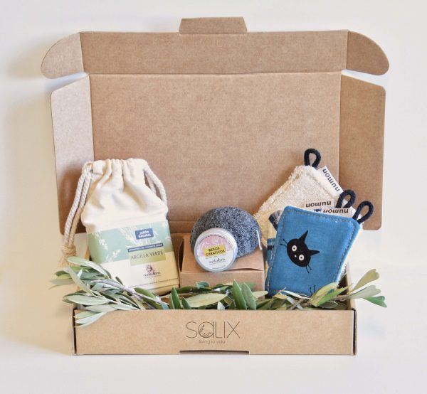 Caja de cartón abierta con productos de cosmética en su interior: jabón sólido, bálsamo labial en un tarrito metálico, discos desmaquillantes reutilizables de tela y esponja konjac de color negro