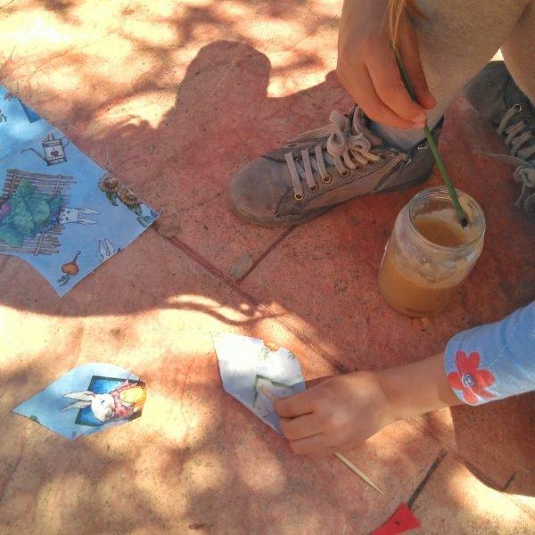 Niña con pinces y telas en el suelo