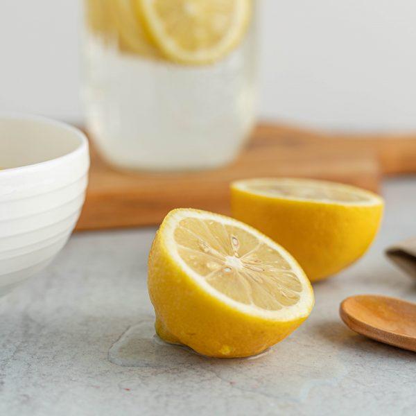 limones cortados en primer plano y bote con agua y limones flotando, sobre una tabla de madera al fondo