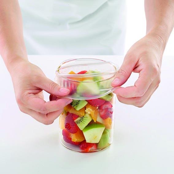 Colocación tapa de silicona en un envase con fruta