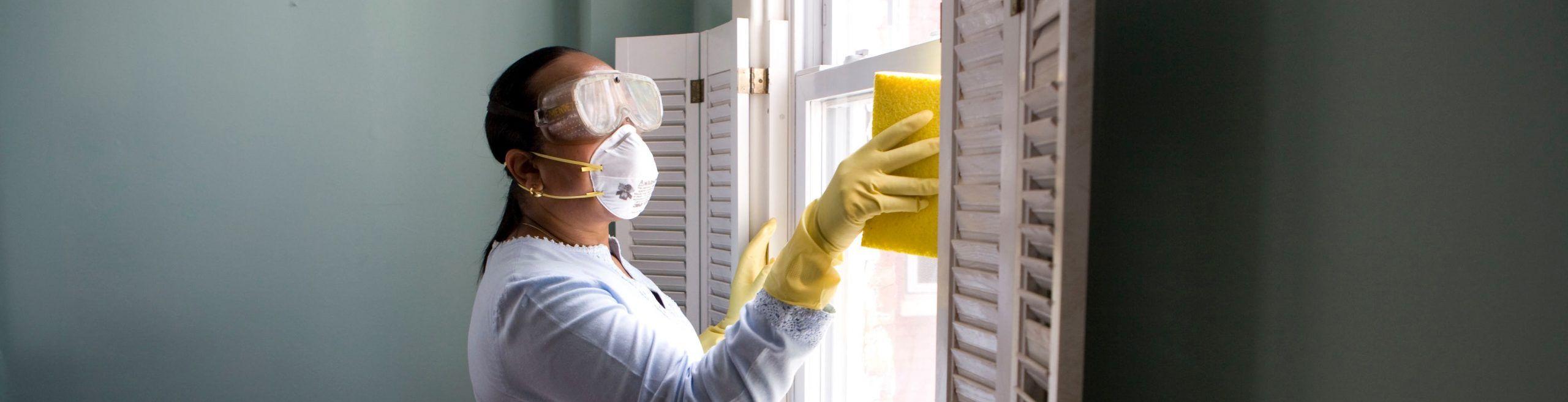 mujer limpiando con guantes, gafas y mascarilla